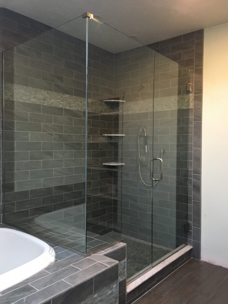 Frameless shower enclosure with knee wall and return that separates the shower and the soaking tub.