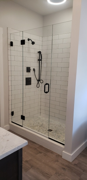 Frameless shower enclosure with side lites. The hardware is oil rubbed bronze.