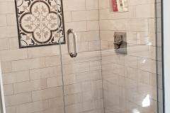 Frameless shower enclosure with brushed nickel hardware